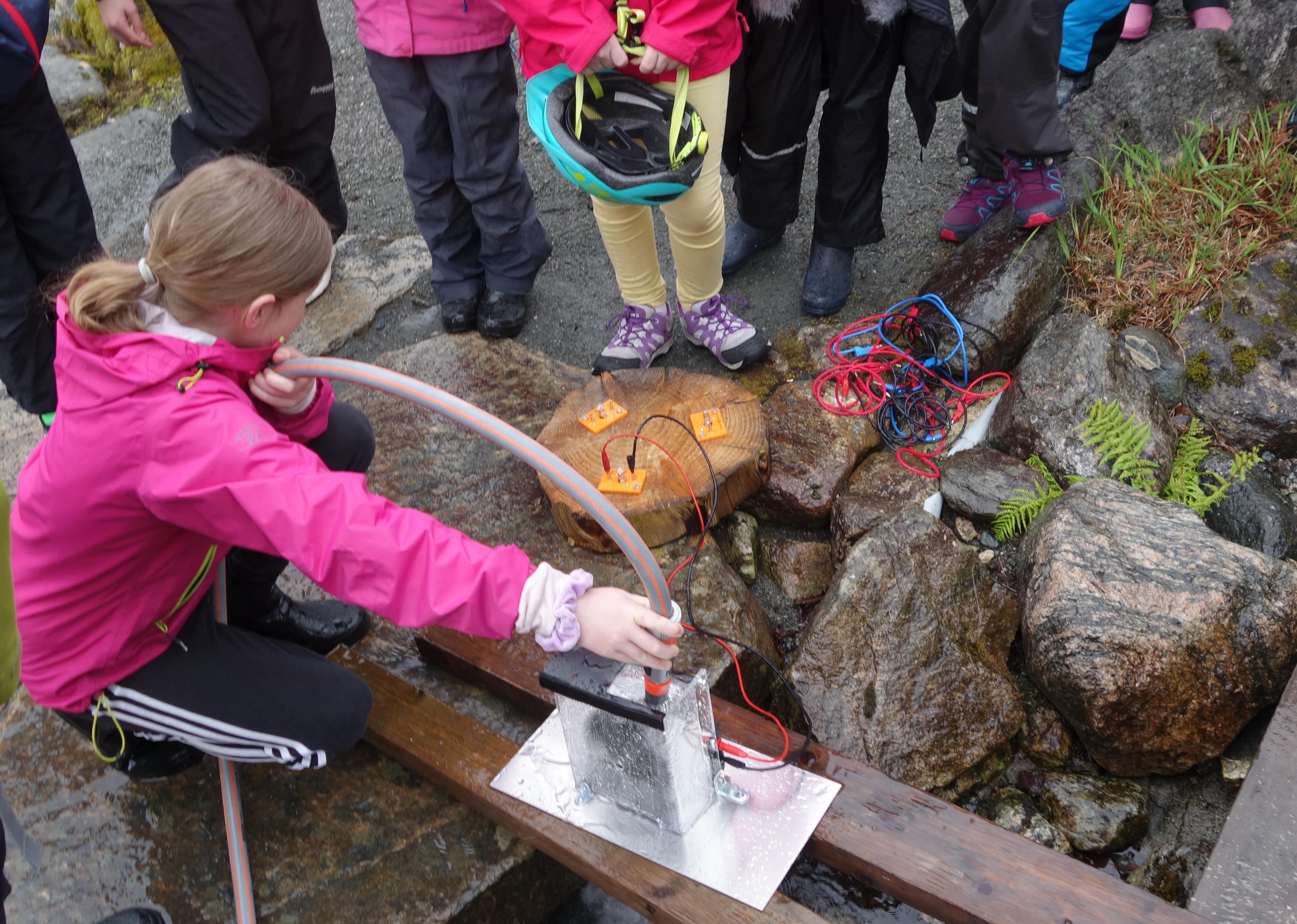 Barn bruker vasslange for å få drift på eit lite kraftverk